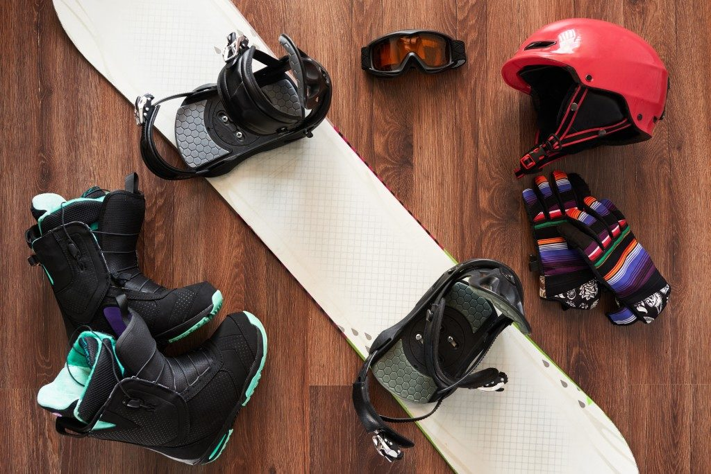 set of snowboard equipment boots, helmet, gloves and mask on a wooden floo