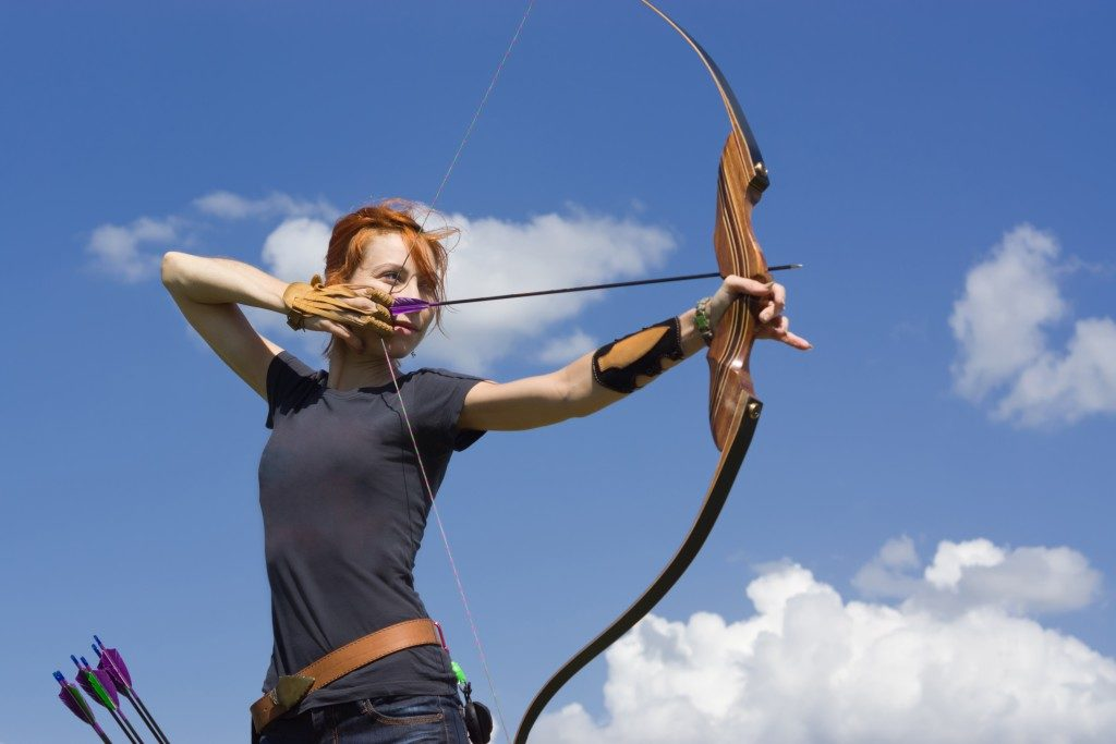 Woman practicing archery in the field