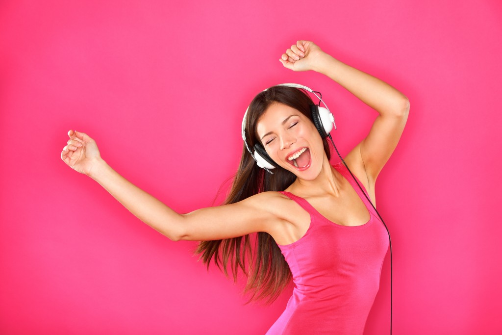 Woman dancing in pink background with headphones